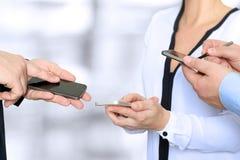 Chiuda su degli uomini e della donna di affari che per mezzo degli Smart Phone mobili Fotografie Stock