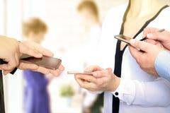 Chiuda su degli uomini e della donna di affari che per mezzo degli Smart Phone mobili Fotografie Stock Libere da Diritti