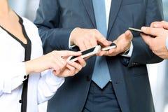 Chiuda su degli uomini e della donna di affari che per mezzo degli Smart Phone mobili Immagini Stock