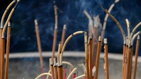Chiuda su dei bastoni di incenso che bruciano in vaso gigante davanti al tempio buddista stock footage