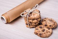 Chiuda su dei biscotti di pepita di cioccolato e della carta pergamena su di legno Fotografia Stock