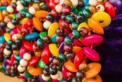 Chiuda su dei braccialetti intrecciati di legno variopinti luminosi con le perle al mercato di strada Immagini Stock Libere da Diritti