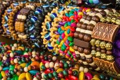 Chiuda su dei braccialetti intrecciati di legno variopinti luminosi con le perle al mercato di strada Fotografia Stock