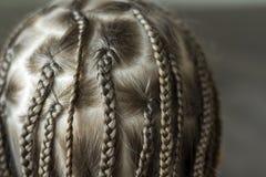 Chiuda su dei capelli della treccia della bambina immagine stock