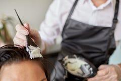 Chiuda su dei capelli di coloritura dello stilista al salone Fotografia Stock