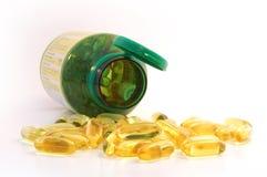 Chiuda in su dei caplets dell'olio di pesce che si rovesciano fuori dal vaso Immagini Stock Libere da Diritti