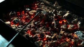 Chiuda su dei carboni rossi che sono misti dal rastrello nero in barbecue, movimento lento stock footage