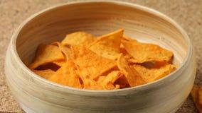 Chiuda su dei chip del nacho che cadono nella ciotola stock footage
