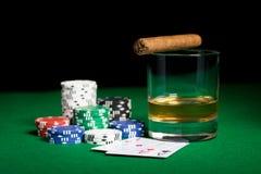 Chiuda su dei chip, delle carte whiskey e del sigaro sulla tavola Fotografia Stock