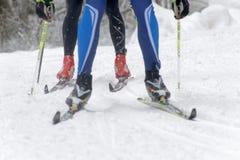 Chiuda su dei cieli, dei piedi e delle gambe variopinti veloci di uno sciatore del paese trasversale Fotografie Stock