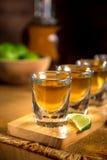 Chiuda su dei colpi di tequila raggruppati insieme ad una bottiglia e tagli le calce su una superficie di legno Fotografia Stock Libera da Diritti