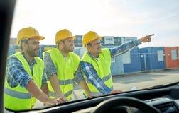 Chiuda su dei costruttori con il modello sul cappuccio dell'automobile Immagini Stock Libere da Diritti