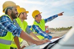 Chiuda su dei costruttori con il modello sul cappuccio dell'automobile Immagine Stock