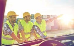Chiuda su dei costruttori con il modello sul cappuccio dell'automobile Fotografie Stock