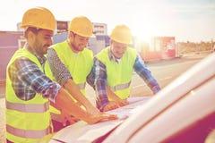 Chiuda su dei costruttori con il modello sul cappuccio dell'automobile Fotografia Stock Libera da Diritti