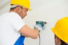Chiuda su dei costruttori con il trapano che perfora la parete Fotografie Stock