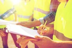 Chiuda su dei costruttori in maglie che scrivono alla lavagna per appunti Fotografia Stock