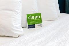Chiuda su dei cuscini lanuginosi bianchi molli sul letto Immagini Stock
