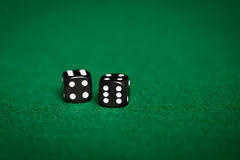 Chiuda su dei dadi neri sulla tavola verde del casinò Immagine Stock