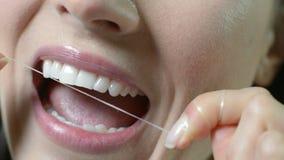 Chiuda su dei denti bianchi Flossing della donna video d archivio