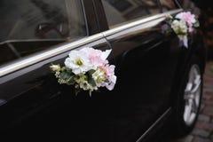 Chiuda su dei dettagli reali alle nozze - decorazione dei fiori dell'automobile di uno sposo e di una sposa immagine stock