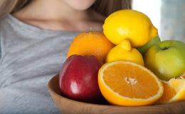Chiuda su dei frutti in ciotola di legno Sano Kiwi, limone, arancia, mele composte in ciotola di legno e tenute dalla giovane don Fotografie Stock