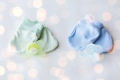 Chiuda su dei guanti e dei soothers del bambino per i gemelli Immagine Stock Libera da Diritti