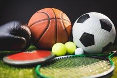 Chiuda su dei guantoni da pugile e palle da golf e disco del tennis di calcio di pallacanestro Fotografia Stock