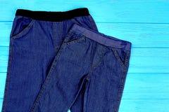Chiuda su dei jeans blu scuro di allungamento per il bambino Immagini Stock