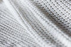 Chiuda su dei lavori o indumenti a maglia bianchi piegati Fotografia Stock