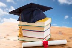 Chiuda su dei libri con il diploma ed il tocco Fotografia Stock Libera da Diritti