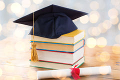 Chiuda su dei libri con il diploma ed il tocco Fotografia Stock