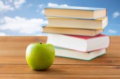 Chiuda su dei libri e della mela verde sulla tavola di legno Immagini Stock