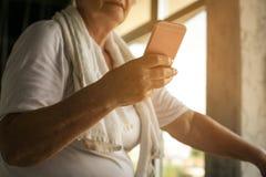 Chiuda su dei messaggi di battitura a macchina della donna senior Fotografia Stock