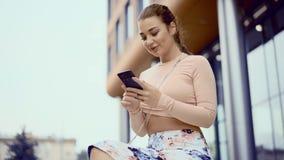 Chiuda su dei messaggi mandanti un sms della giovane donna attraente sul telefono cellulare video d archivio