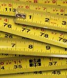 Chiuda in su dei nastri di misurazione gialli del metallo Immagini Stock
