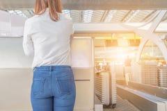 Chiuda su dei passeggeri delle giovani donne che controllano ad un cou di linea aerea fotografia stock