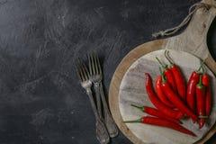 Chiuda su dei peperoncini rossi rossi freschi sul tagliere di legno Fotografia Stock Libera da Diritti