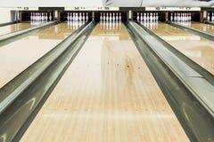 Chiuda su dei perni di bowling in una fila Immagini Stock