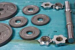 Chiuda su dei piatti metallici del peso sul pavimento di legno e delle teste di legno nel fondo Fotografia Stock