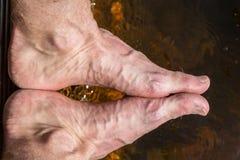 Chiuda su dei piedi approssimativi con le vene, la riflessione in acqua all'aperto Immagini Stock