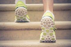 Chiuda su dei piedi con le scarpe da tennis che scalano le scale Fotografie Stock