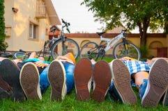 Chiuda su dei piedi degli adolescenti in scarpe da tennis mentre si trovano sull'erba Immagini Stock Libere da Diritti