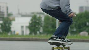 Chiuda su dei piedi dei skateboarder mentre pattinano sul calcestruzzo al parco del pattino stock footage