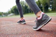Chiuda su dei piedi della donna che corrono sulla pista dalla parte posteriore Immagine Stock Libera da Diritti