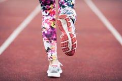 Chiuda su dei piedi delle ragazze in scarpe da tennis e calzamaglia, correndo su una pista corrente speciale con un rivestimento  Fotografia Stock