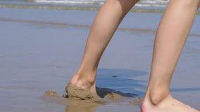 Chiuda su dei piedi nudi di una persona che camminano ad una bella spiaggia tropicale archivi video