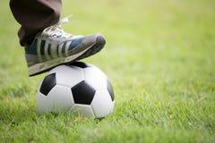 Chiuda su dei piedi sopra pallone da calcio Fotografia Stock Libera da Diritti