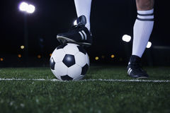 Chiuda su dei piedi sopra pallone da calcio sulla linea, notte nello stadio Fotografia Stock