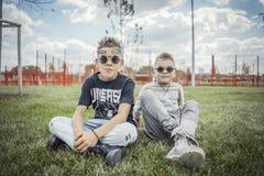 Chiuda su dei ragazzi che si siedono nel parco sull'erba verde Concetto 'nucleo familiare' felice immagini stock